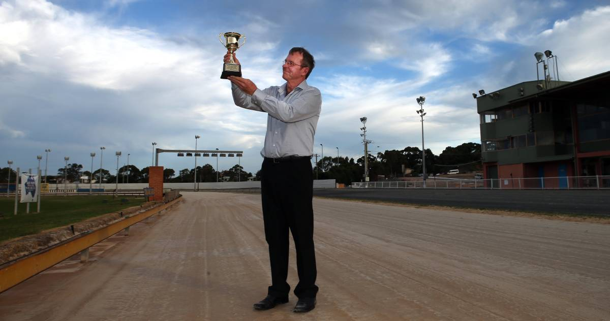EYES ON THE PRIZE: Bulli Greyhounds manager Darren Hull holds up the Cyril Rowe Bulli Cup before a past race meeting. Picture: Kirk Gilmour