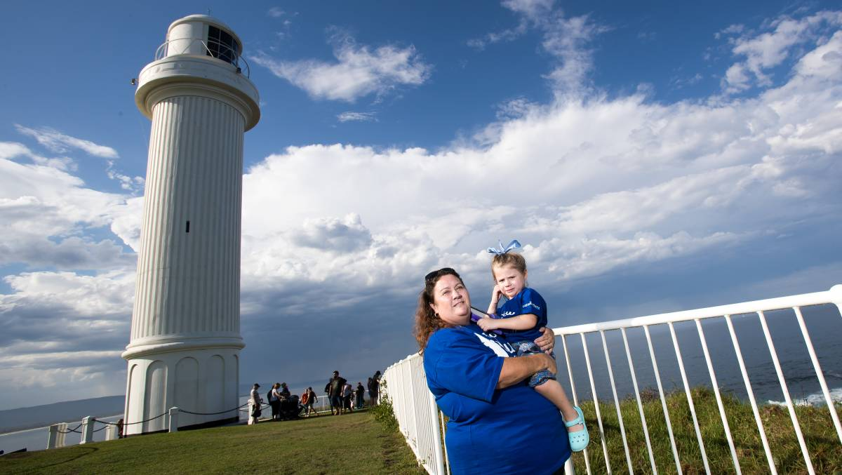 Raising awareness: Kylie O'Neill with daughter Grace at Wollongong Lighthouse, which turned blue on Monday night. Picture: Adam McLean