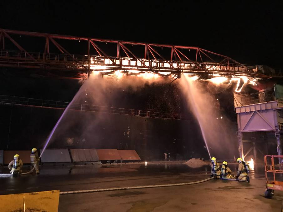 HARD TO GET AT: Firefighters train hoses on a conveyor belt attached to the Iron Chieftain, in the early stages of the firefighting effort last week. Picture: Supplied