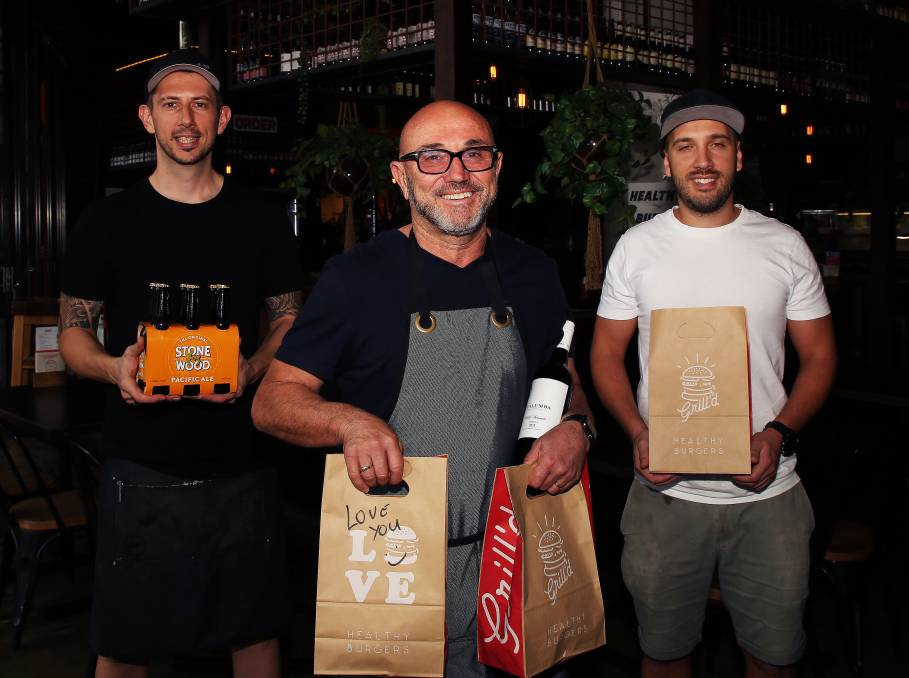 Special permission: Lube Markovski with his son-in-law Robert Gorgievski and son Allen Markovski standing two metres behind can now deliver a six pack of beer or bottle of wine with each Grill'd meal.