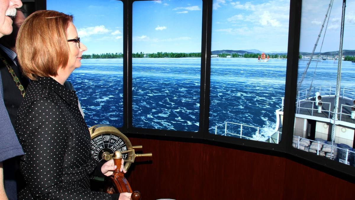 GOING, GOING, GONE: Prime Minister Julia Gillard tries her hand at taking the controls of the S.S. Woniora simulator but ends up sinking the virtual ship in Devonport yesterday. Photos: STUART WILSON